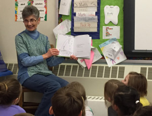 Diane Buyer reads to first grade students as a classroom volunteer at Genet Elementary School.