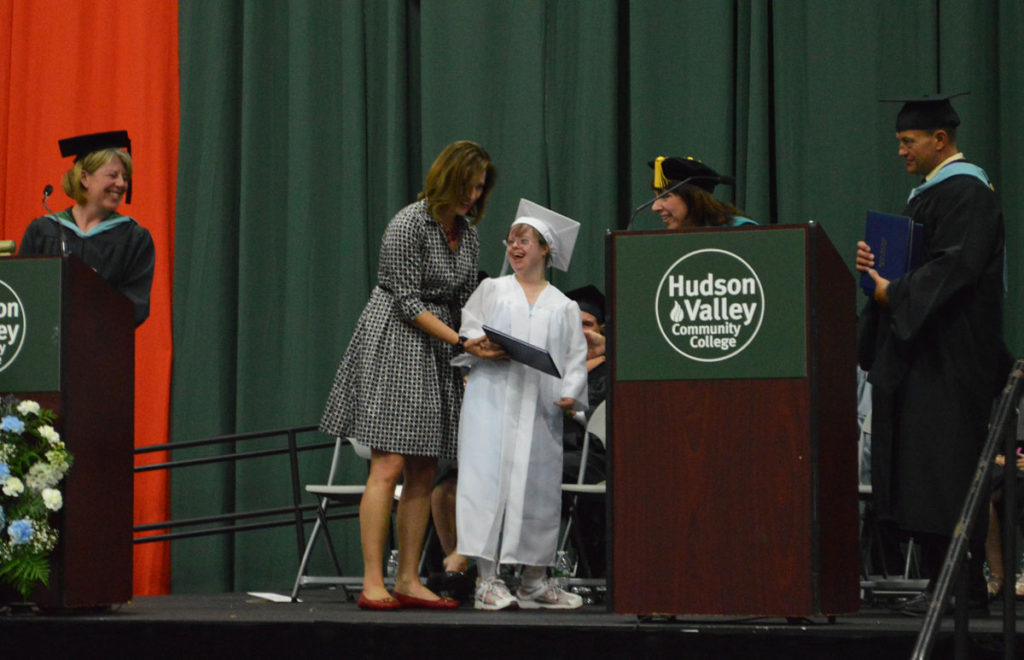Kathleen Grace '16 accepts her diploma with assistance from Green Meadow first grade teacher Denise Romer.