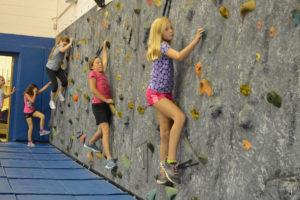 Students climb rock wall