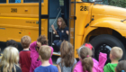 Marie Noeth talks to students in front of school bus