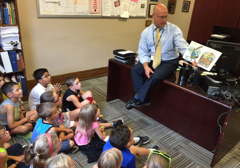 Mr. Mahar reads to 2nd graders in his office.