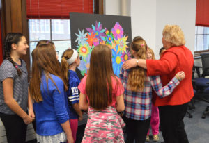Mrs. Yeomans admires the artwork with students who created it.