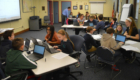 Student advisory council works on chromebooks in conference room