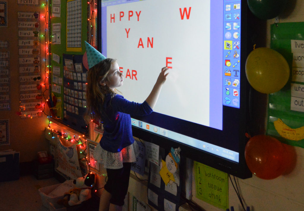 "A student re-arranges letters from the phrase ""Happy New Year."""