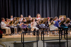 Students play instruments on stage