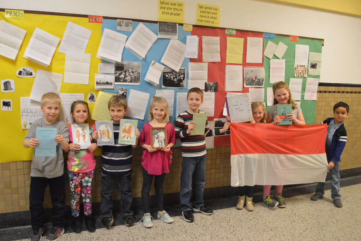 Genet first graders stand in front of their research display