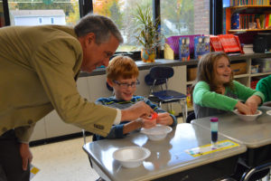Mr. Caporta visits a classroom conducting science experiments.