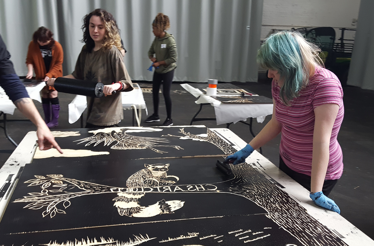 Columbia students roll ink onto their design