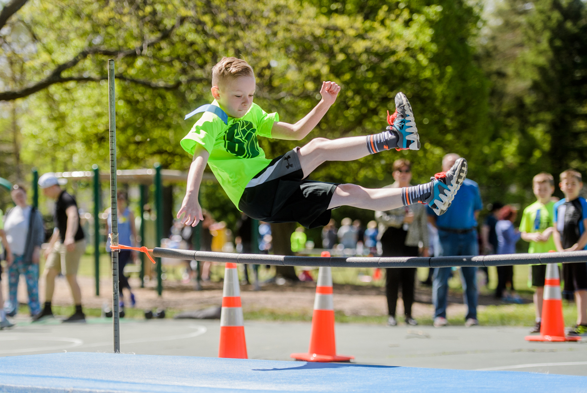 A student clears the bar in the high jump event