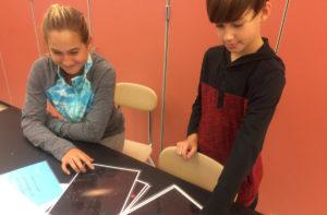 Students look at photos of galaxies