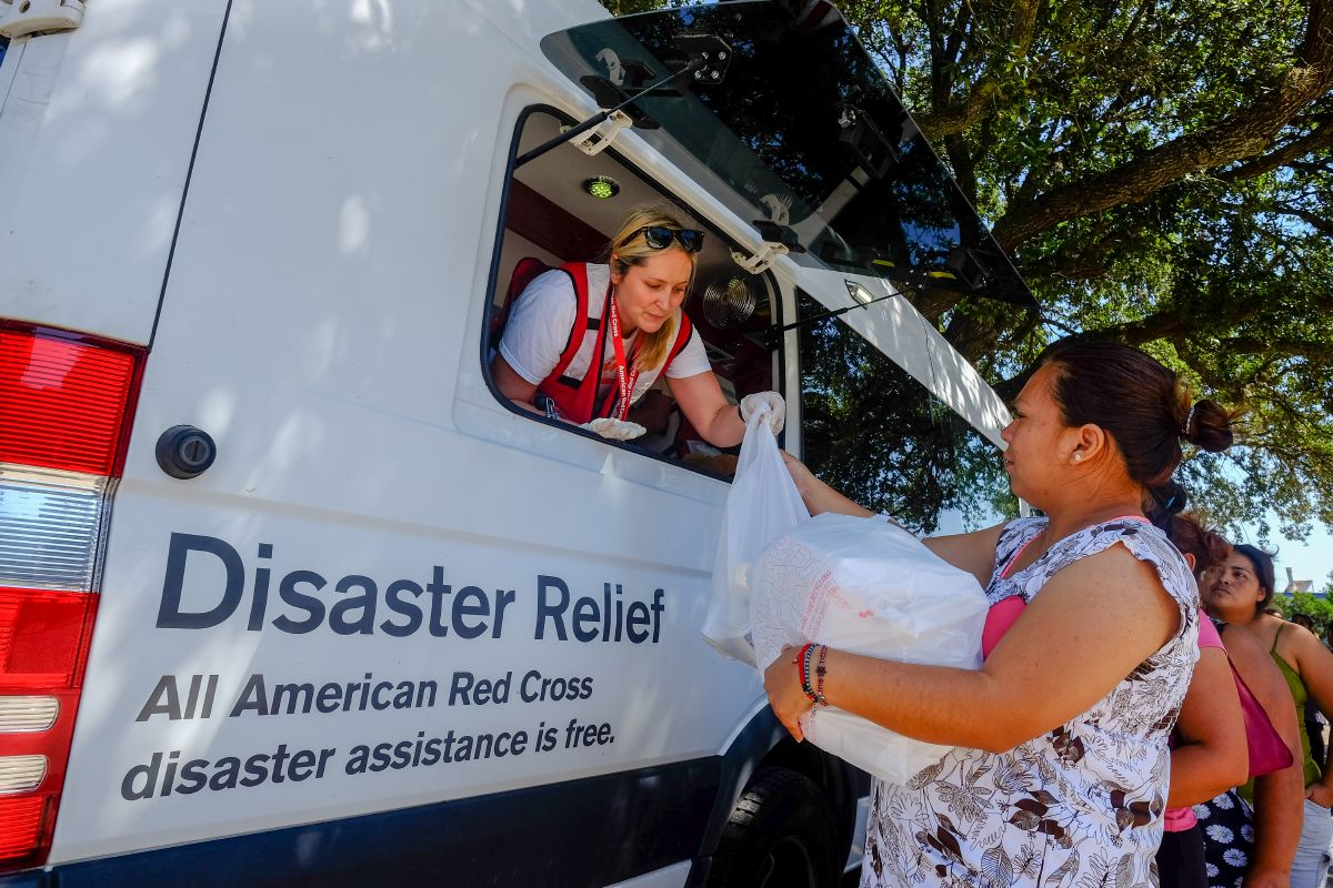 Red Cross volunteer Katie Bossc gives lunch to Jessica Guzma from an Emergency Response Vehicle