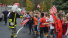 Sparky gives high fives to students at Bell Top