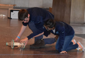 Fritz Howard and Abby Radin work on their Mousetrap vehicle at the MIT Invitational.