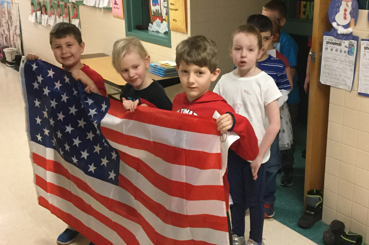 DPS students holding American flag for Olympic ceremony