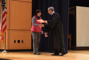 A new U.S. citizen receives a certificate at her naturalization ceremony