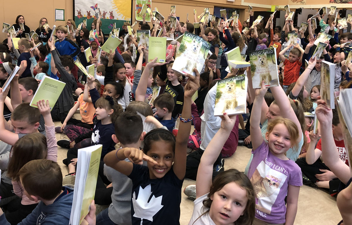 Students hold up their books