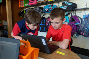 Students work together on a Chromebook