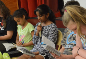 Student reads at Bell Top Book Club assembly