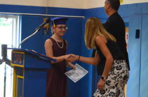 Student shakes hands with Mrs. Adams