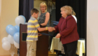 Student receives certificate from Principal Yeomans