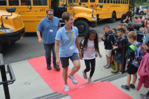 Bus drivers walk on a red carpet into Bell Top