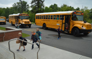 Students walk from bus to school entrance
