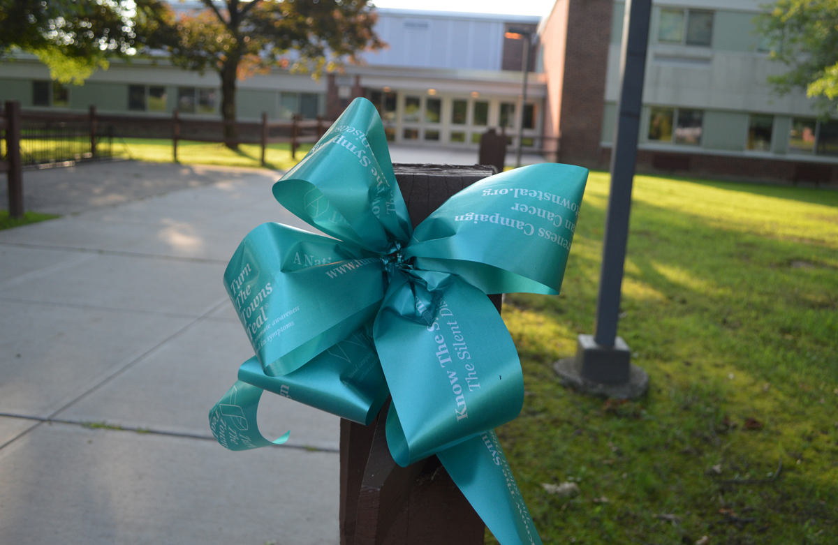 A teal ribbon is fastened to the fence leading up to Howard L. Goff Middle School