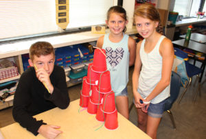 Students build a pyramid of plastic cups