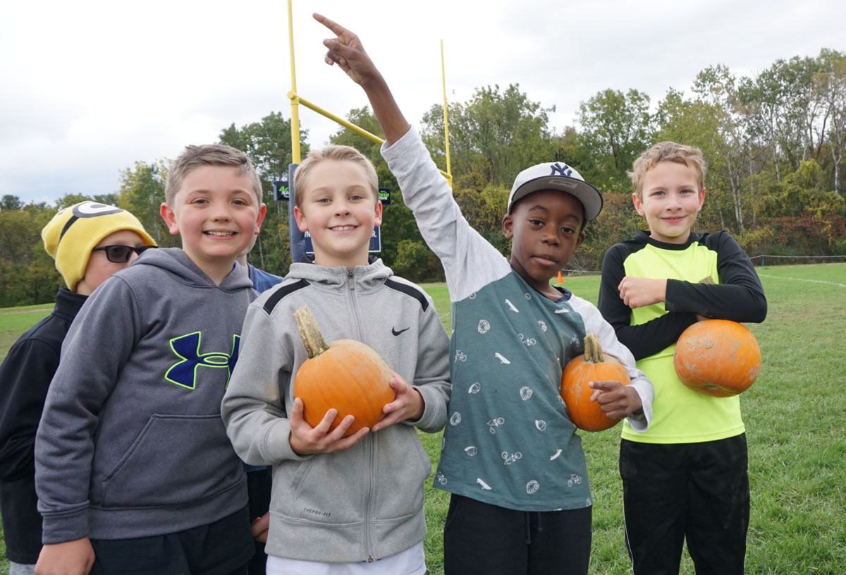 Students holding pumpkins