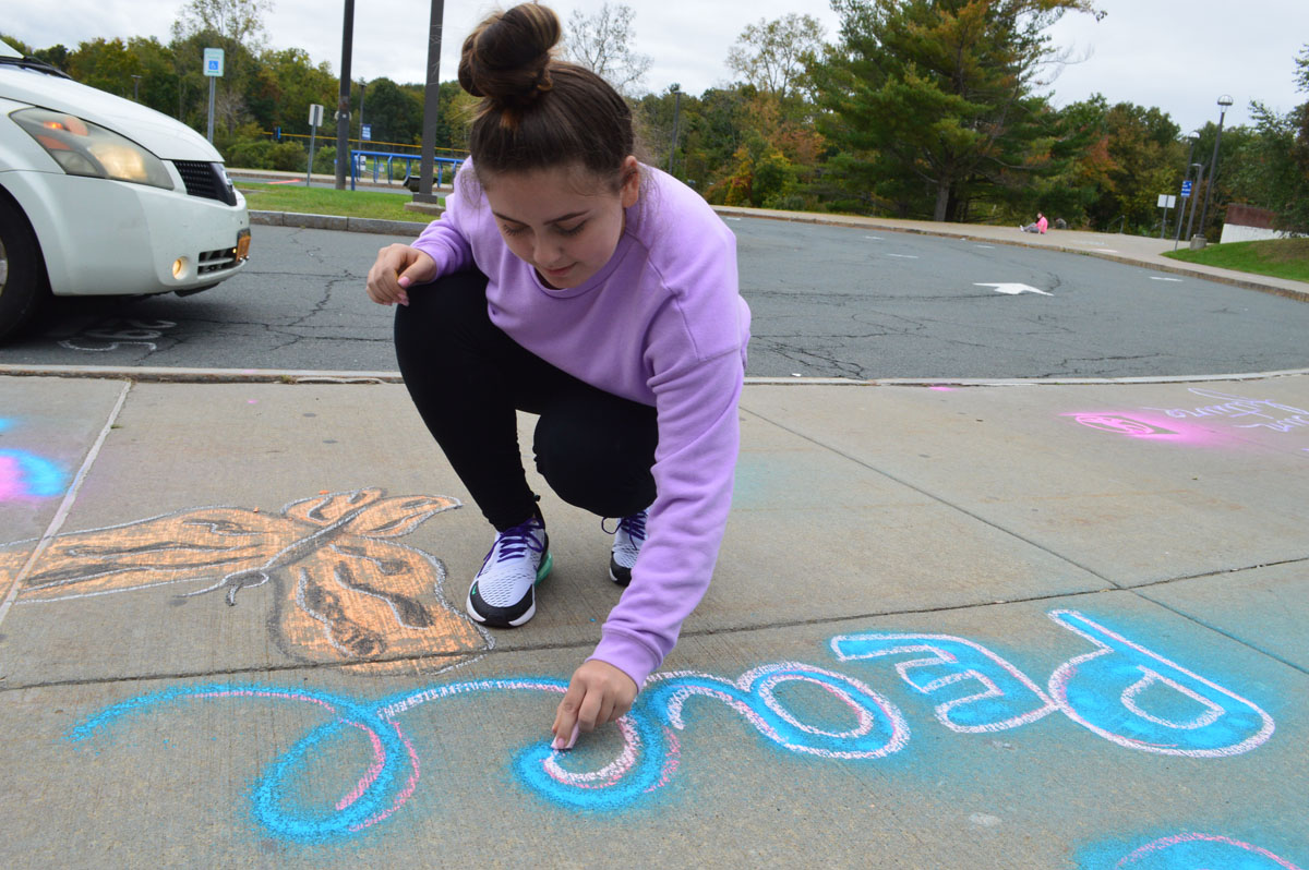 Student drawing with sidewalk chalk