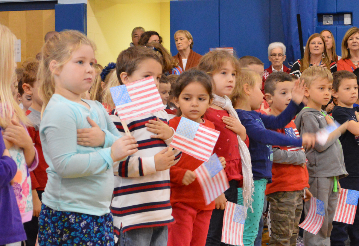 Students holding flags at Veterans Day assembly