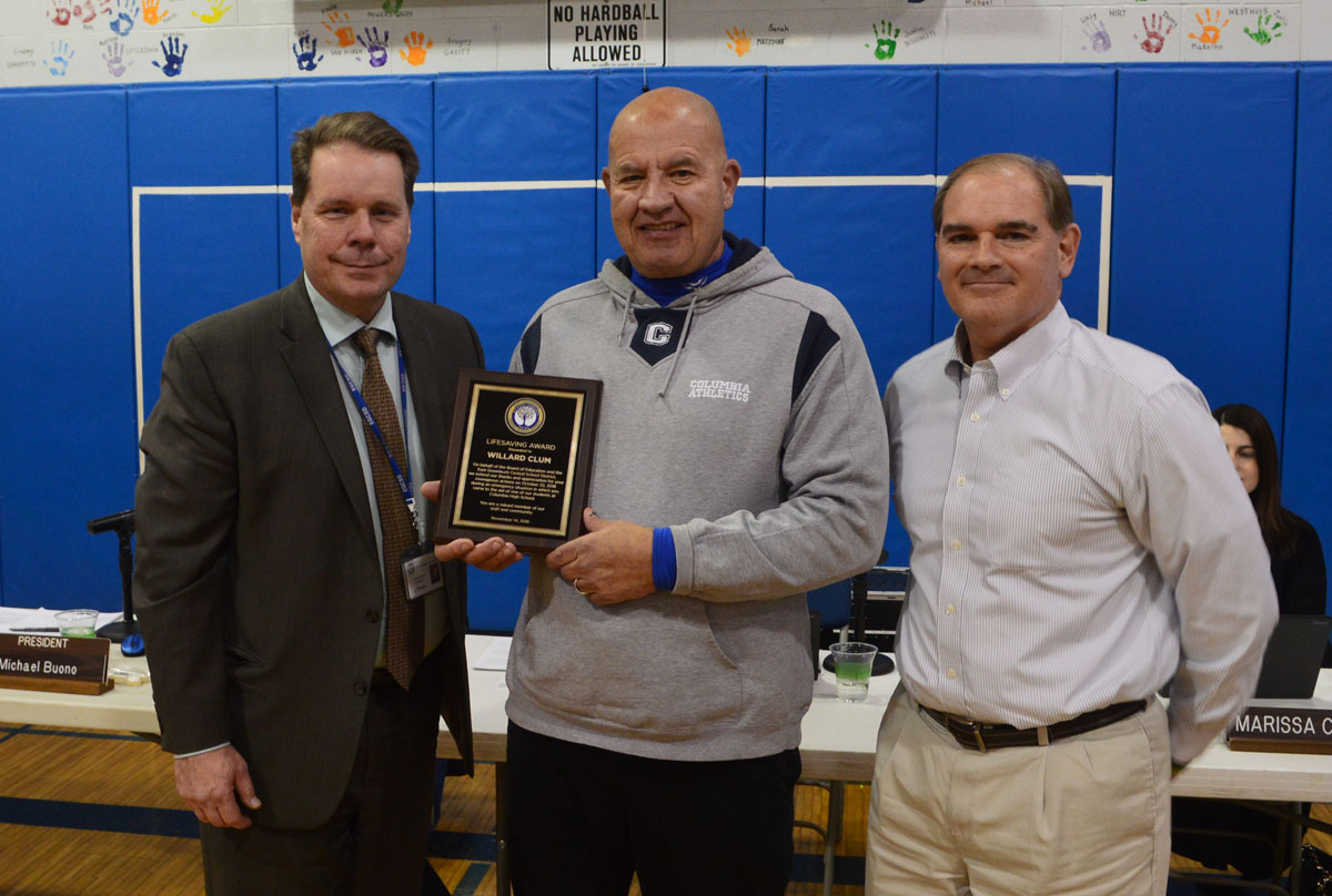 Columbia High School monitor Bill Clum receives the Lifesaving Award from Superintendent Jeff Simons and Board of Education President Michael Buono.