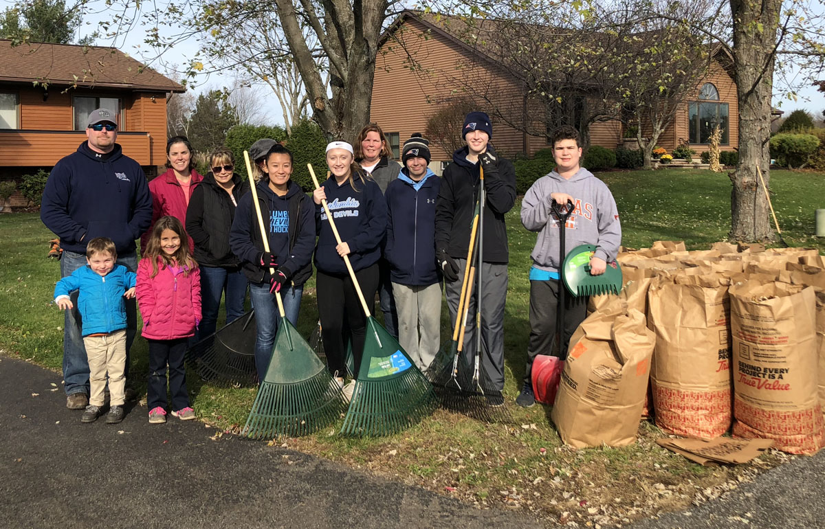 Teachers and students raking leaves for local veterans