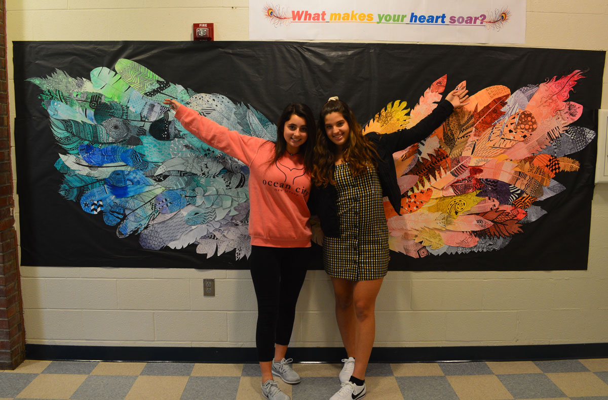 Students pose in front of feather mural at Columbia