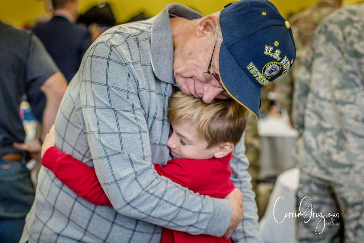 Student hugging veteran after assembly