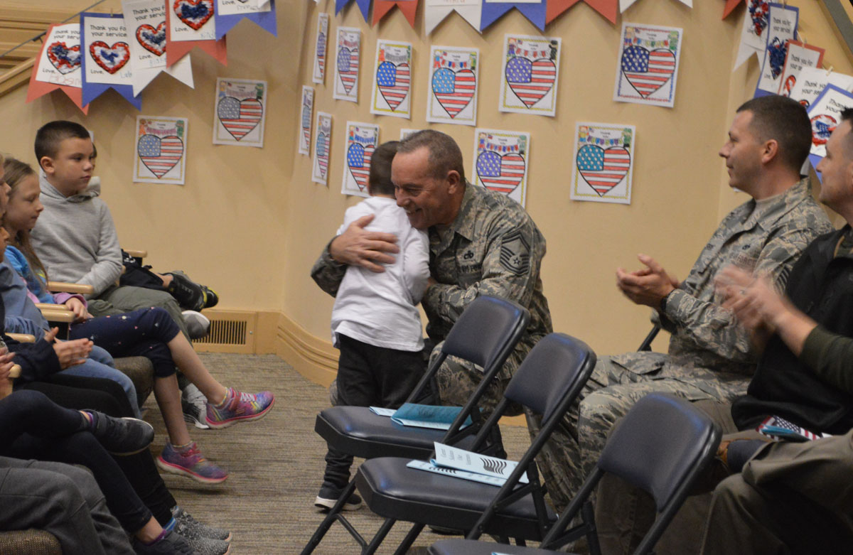 Student hugging veteran at assembly