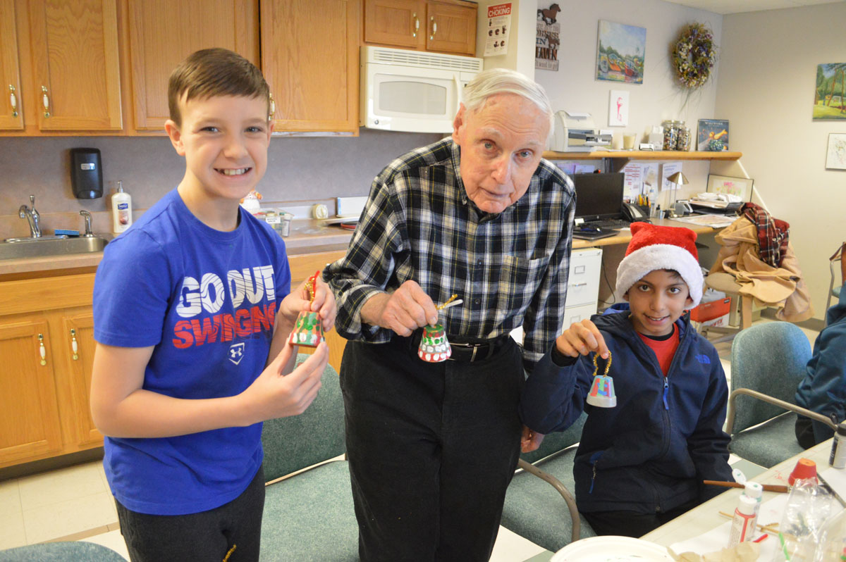 Students and a senior hold Christmas ornaments