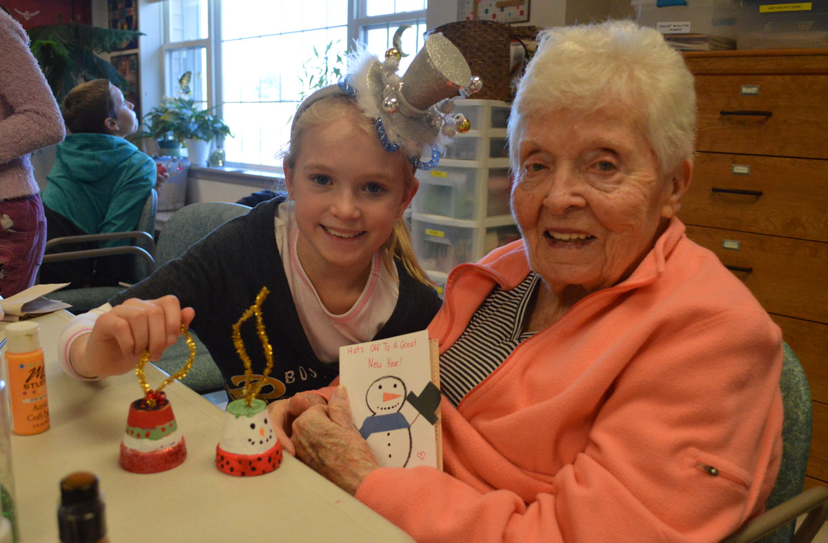 Kaelynn Stringer, a 6th grader from Howard L. Goff Middle School, helps Patricia Finnerty make a Christmas ornament on Tuesday morning at Beverwyck in Slingerlands.