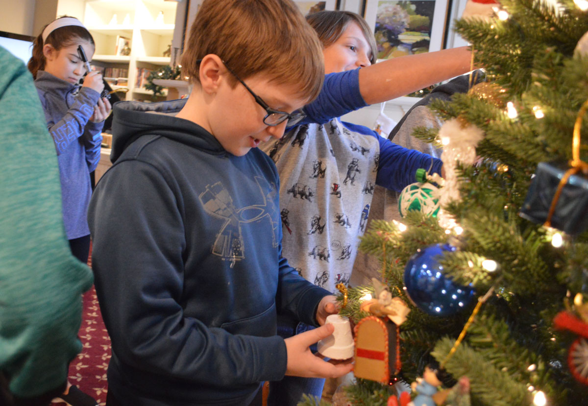 A student places his ornament on the Christmas tree at Beverwyck