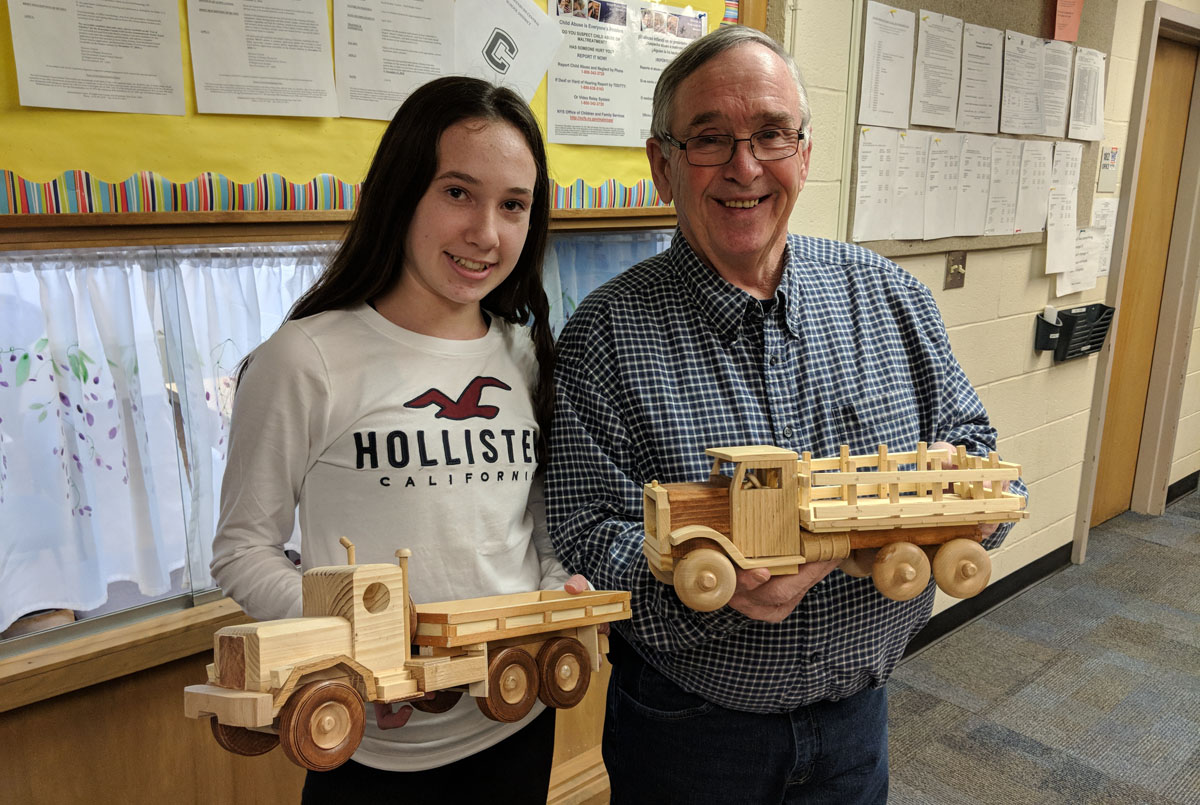 Goff Middle School 8th grader Emily Doherty with her grandpa Jim Hanley who made wooden trucks and cars to be donated to the CoNSERNS-U Christmas Store.