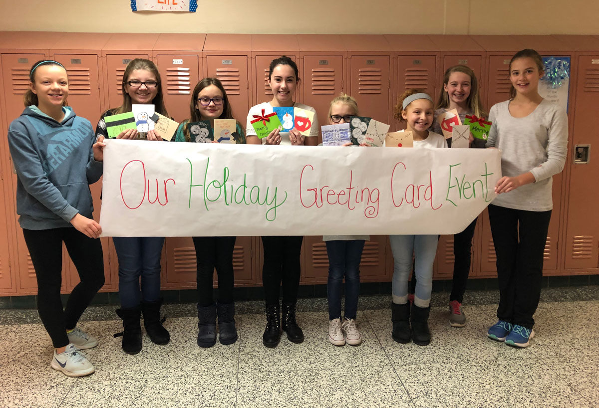 Students holding holiday cards