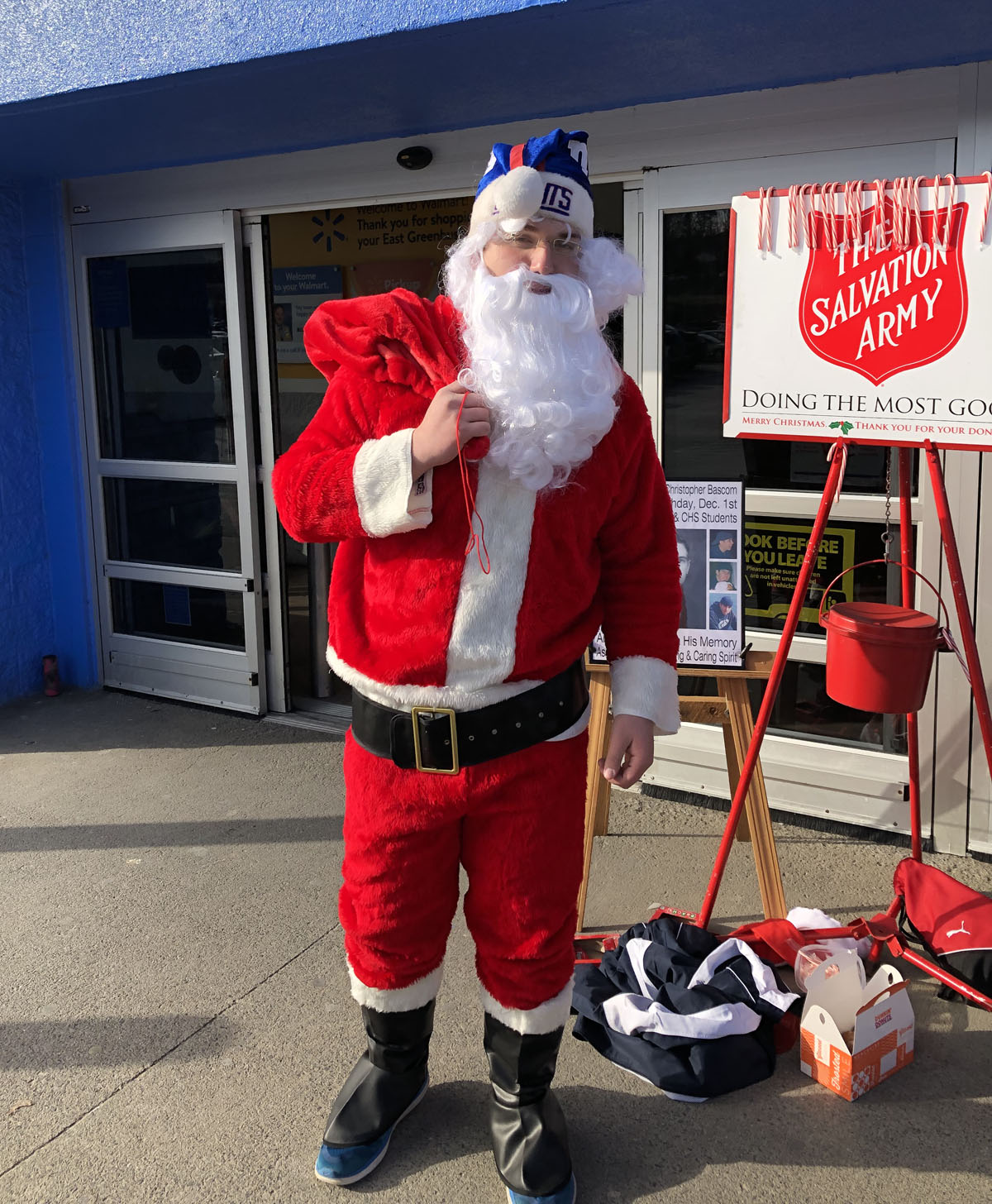Student dressed as Santa Claus collecting money for Salvation Army outside of Walmart