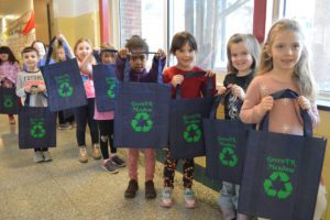 Students holding reusable tote bags