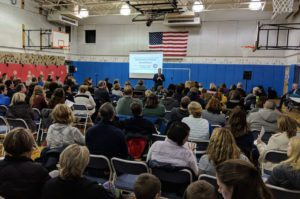 Superintendent Jeff Simons addresses parents in the Bell Top gymnasium