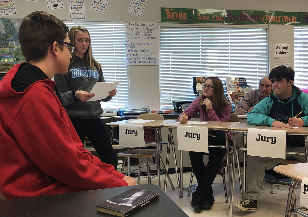 "A student answers questions as a witness in a mock trial based on the novel ""The Outsiders"""