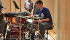 Student playing drums on stage