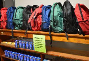 Backpacks lined up on a shelf