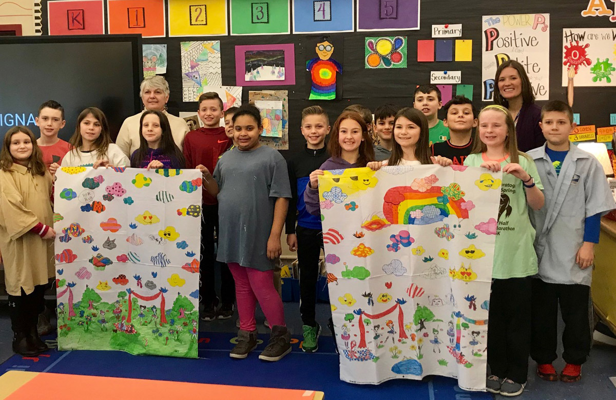 Students hold up pillow cases that they decorated
