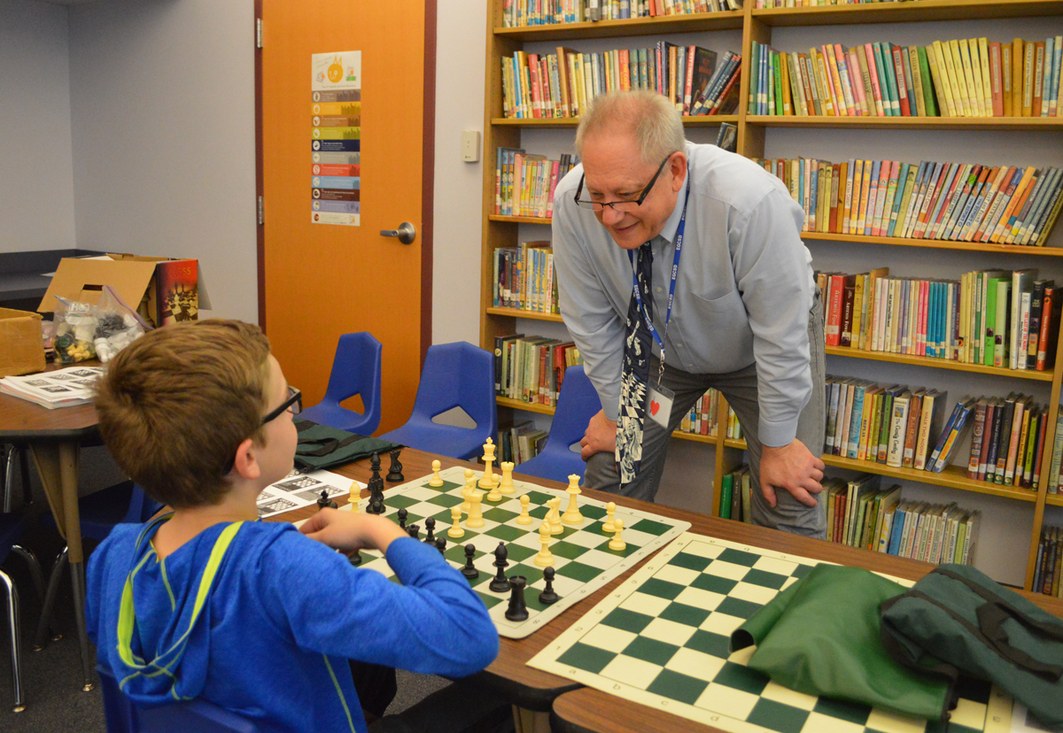 Mr. Kelvin playing chess with student