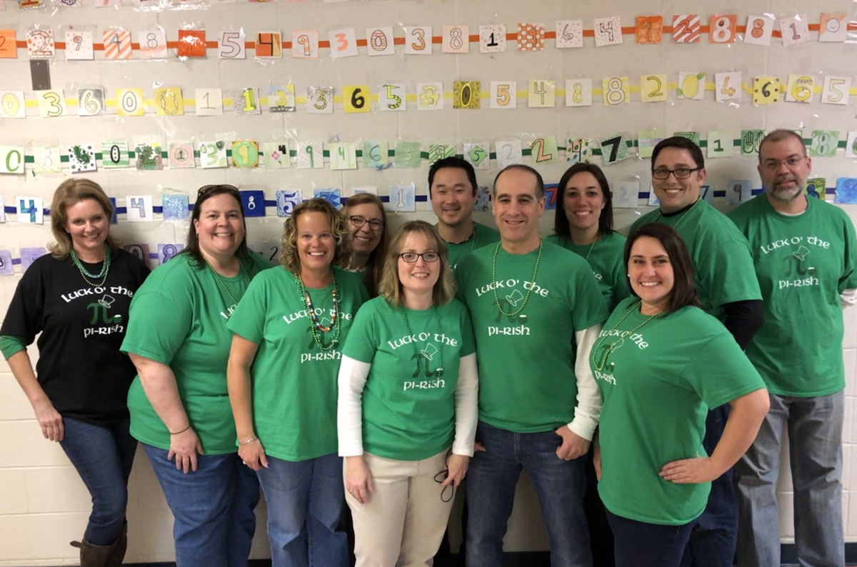 Columbia Math teachers in front of Pi Day display